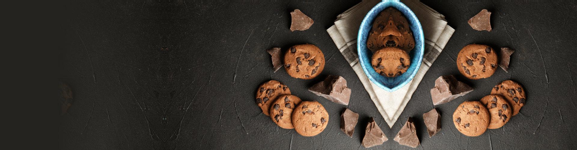 Tasty chocolate chip cookies on dark background, flat lay