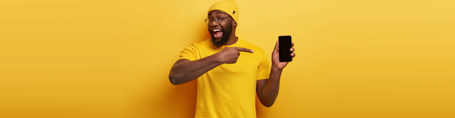 smiling man pointing finger at smartphone screen