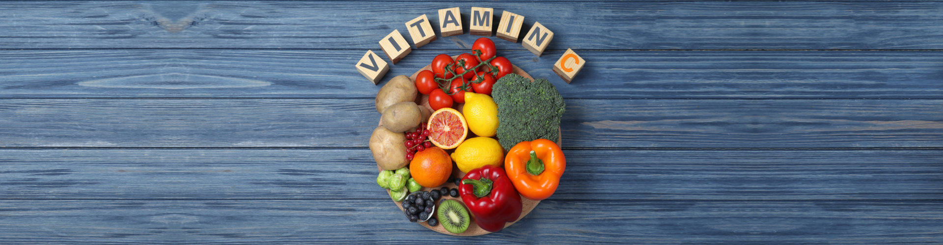 cubes with phrase vitamin c and fresh products on blue wooden table