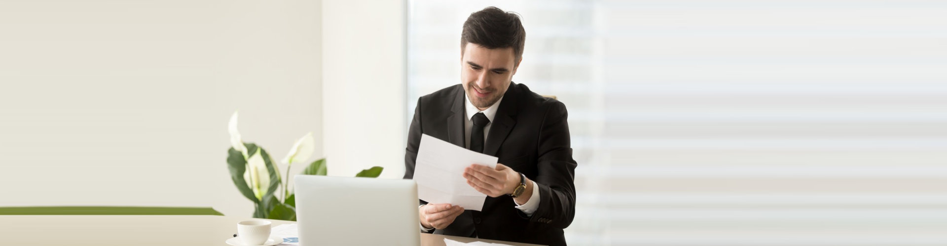 a man looking at the paper and smiling